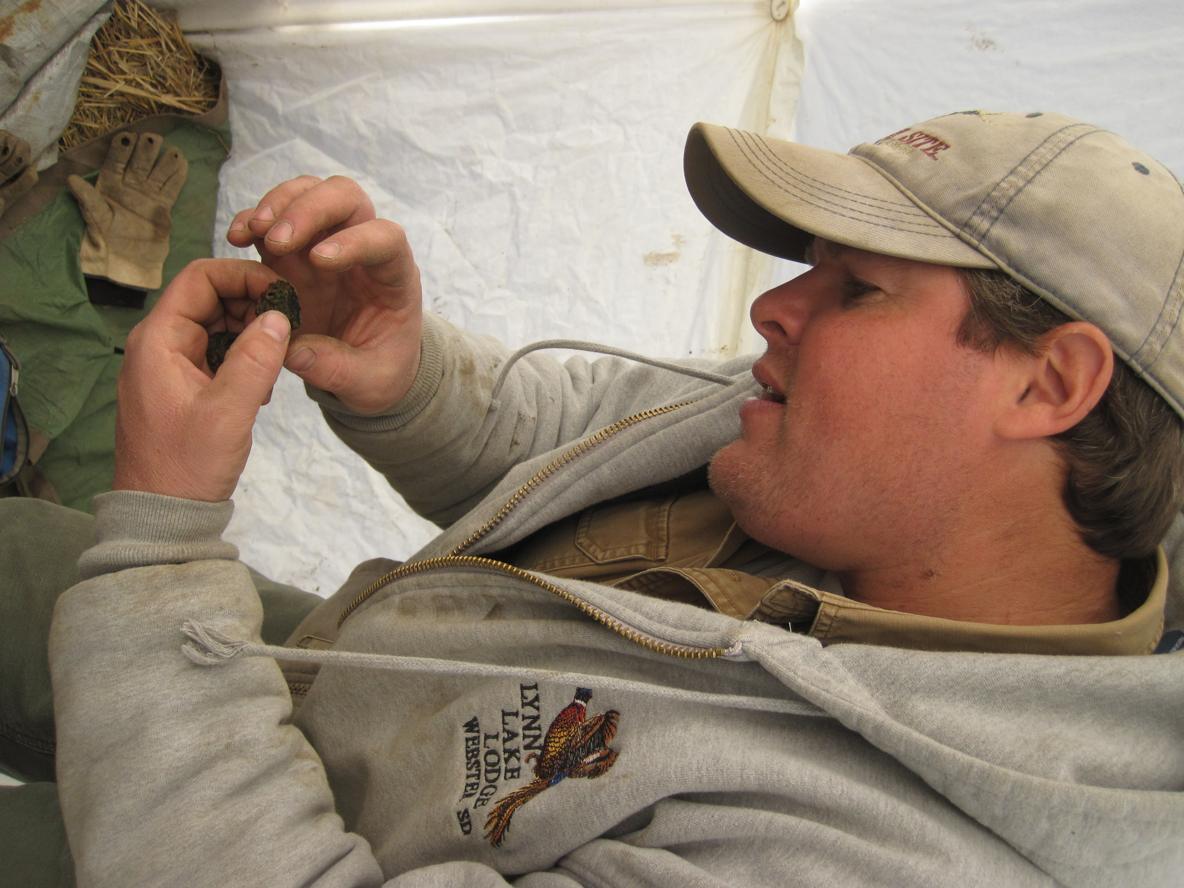 Dan Horgen examines one of the shotgun shells recovered from the privy