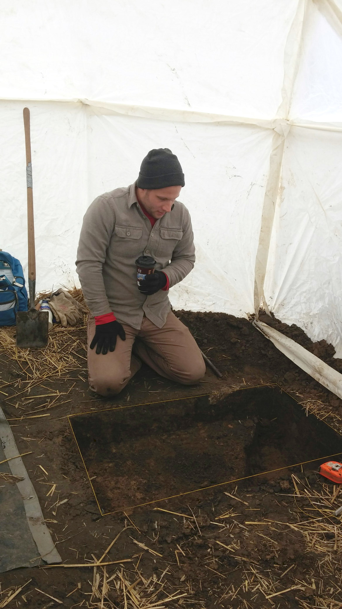 Inside a yurt, Anson Kritsch excavating a historic feature