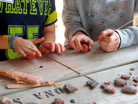 Children making clay pottery