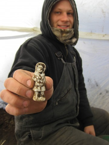 Anson Kritsch holding a white ceramic girl doll found in the privy